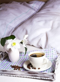 Morning coffee in bed on rustic wooden serving tray