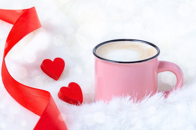 Morning coffee in bed with couple of red hearts and ribbon for st valentine day