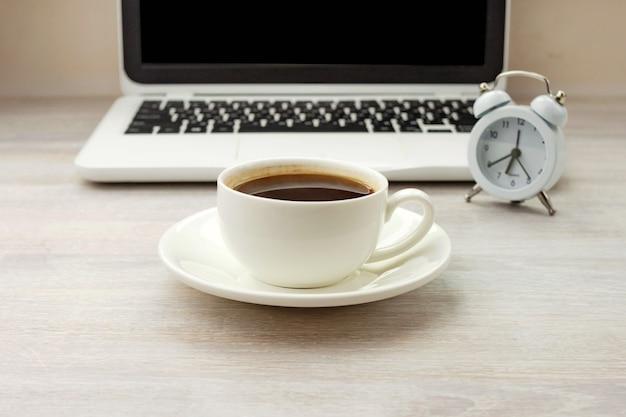 白いカップのモーニングコーヒーブラックホットエスプレッソ、木製テーブルの受け皿、時計、ノートブック。閉じる。側面図。選択的なソフトフォーカス。テキストコピースペース。