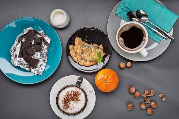 Утренний кофе, сливки, шоколад, орехи, мандарины и выпечка.