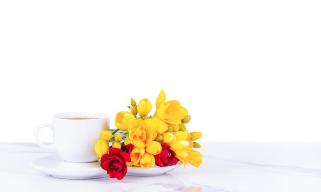 朝のコーヒーカップと白い背景の花