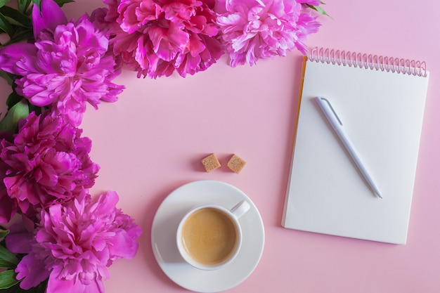 Morning coffee cup for breakfast, empty notebook and pink peony flowers on pink table top