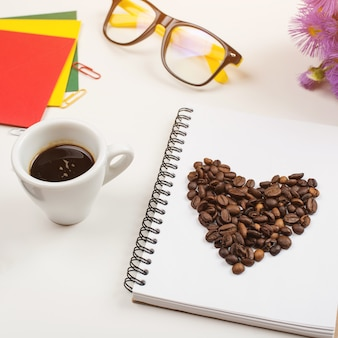 Morning coffee cup, notebook, pencil, glasses and flowers on white table. top view, flat lay.