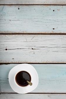 青い木製の背景の朝のコーヒーカップ