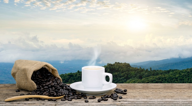 Morning coffee cup and roasted coffee beans views with mountain sun