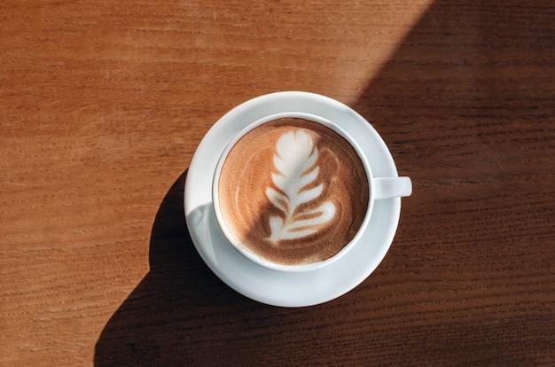 Утренняя кофейная чашка с красивым искусством на ней на деревянном