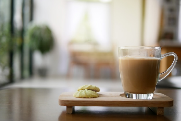Morning coffee cup with two pieces of cookies on wood table in home blurred, drinking coffee before start working from home