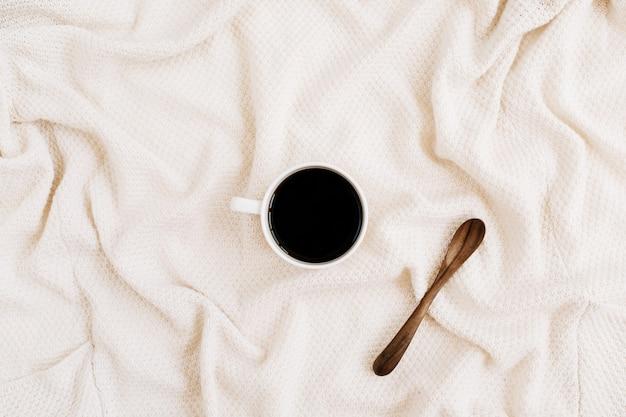 베이지 색 섬유 표면에 나무 숟가락으로 모닝 커피 컵