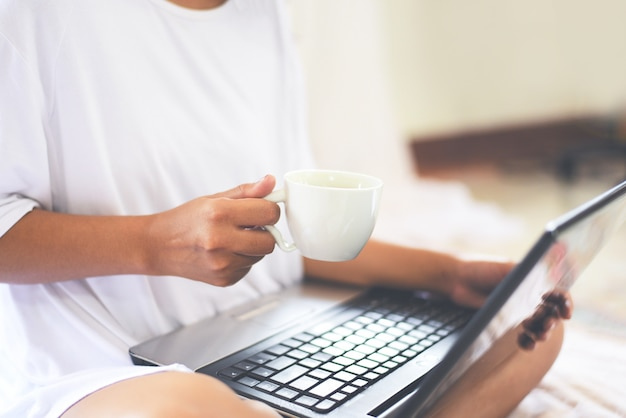 Morning coffee cup  woman holding coffee cup by hand with laptop on the bed