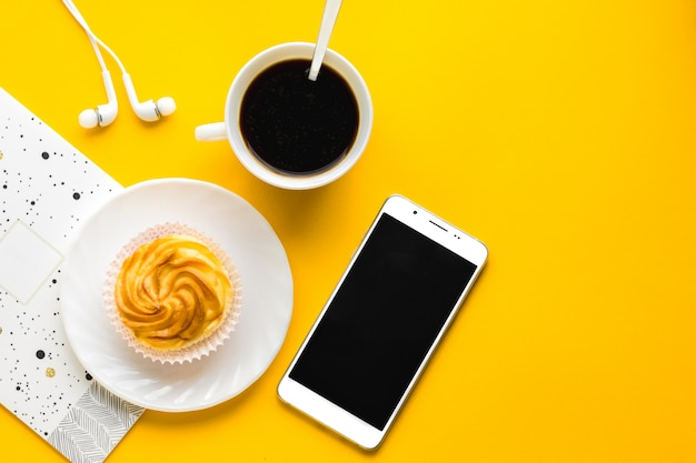 Morning coffee, delicious cake on white plate, mobile. copy space. top view. yellow background. birthday in office background
