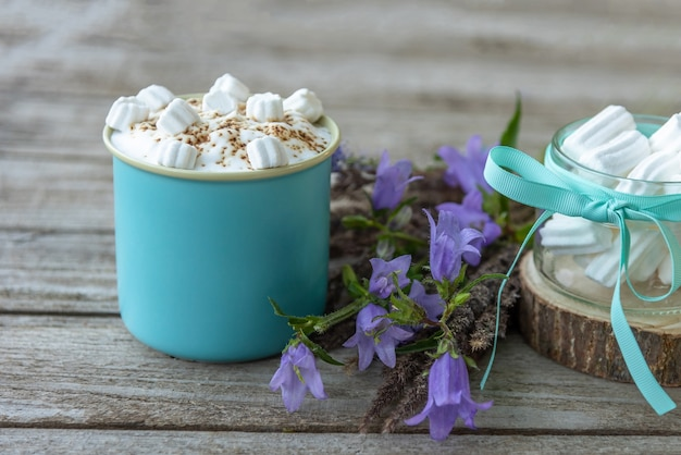 Morning coffee drink with marshmallow slices on a wooden background.