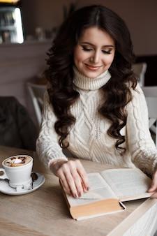 Утренний кофе, наслаждение, она закрыла глаза. удивительная девушка читает книгу и улыбается. читает с интересом. стол с напитком, сладости к чаю.