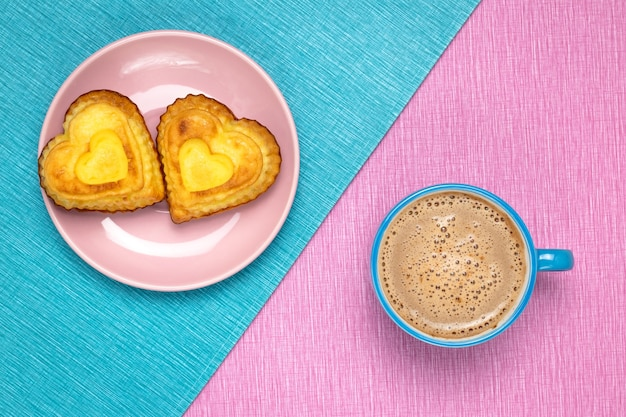 Morning coffee and heart shaped cupcakes on a pink and blue tablecloth.