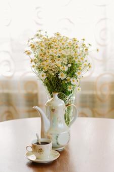 Утренний кофе. чашка горячего кофе и букет ромашек в вазе на круглом деревянном столе на фоне окна