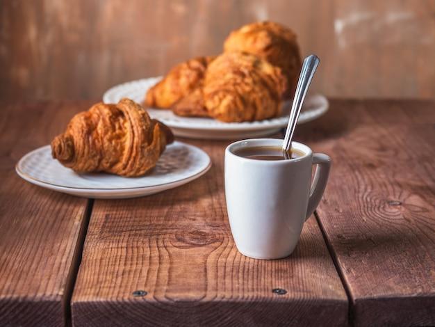 テーブルの上の皿に小さじ1杯とクロワッサンを入れた白いマグカップのモーニングコーヒー