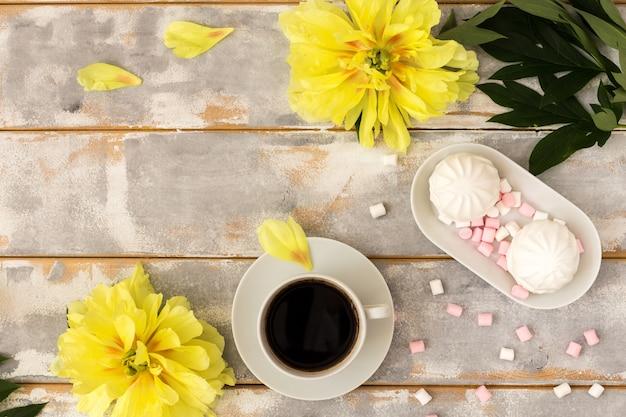Morning coffee, marshmallows and beautiful yellow peony flowers