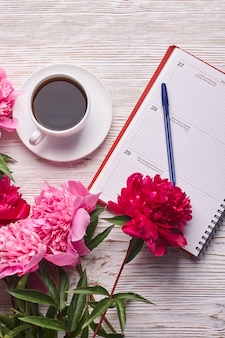 Morning coffee mug for breakfast empty notebook pencil and pink peony flowers on white stone table t...