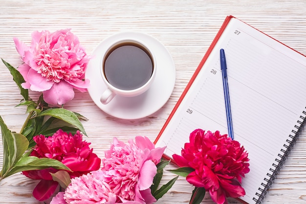 Morning coffee mug for breakfast, empty notebook, pencil and pink peony flowers on white stone table top view in flat lay style.