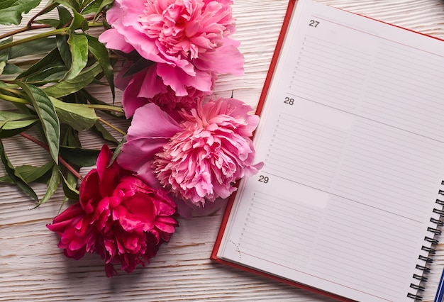 Morning coffee mug for breakfast, empty notebook, pencil and pink peony flowers on white stone table top view