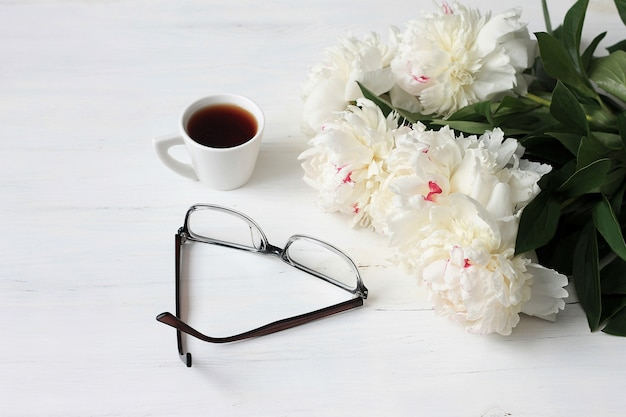 Morning coffee mug, glasses and white peonies flowers on white wooden table