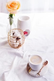 Morning coffee mug with glasses on a notebook, candle and rose on a white bed
