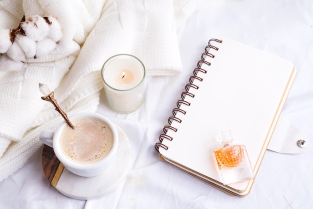 Morning coffee mug with notebook, candle and cotton flowers on a white bed top view