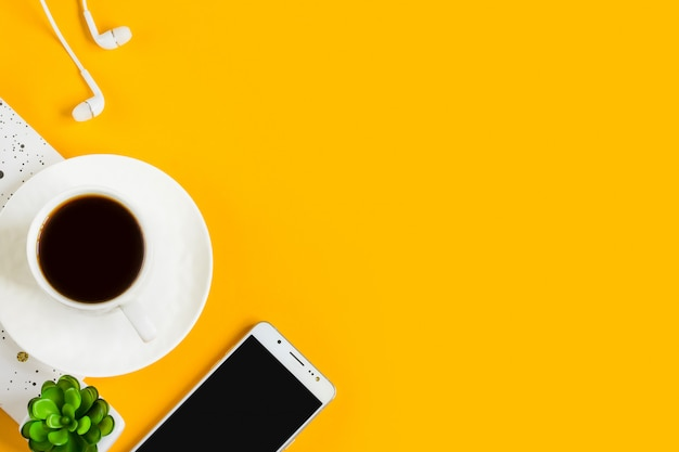 Morning coffee, notebook, mobile phone, plants on a yellow background. business yellow background.