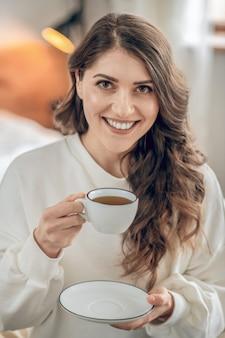 モーニング・コーヒー。ベッドに座ってコーヒーを飲むかなり若い女性