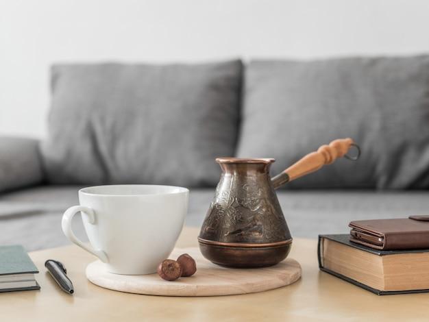 インテリアの朝のコーヒーの静物。コーヒーカップ、cezve、テーブル、灰色のソファの背景の本。家の朝食ドリンクコンセプトをご利用いただけます。