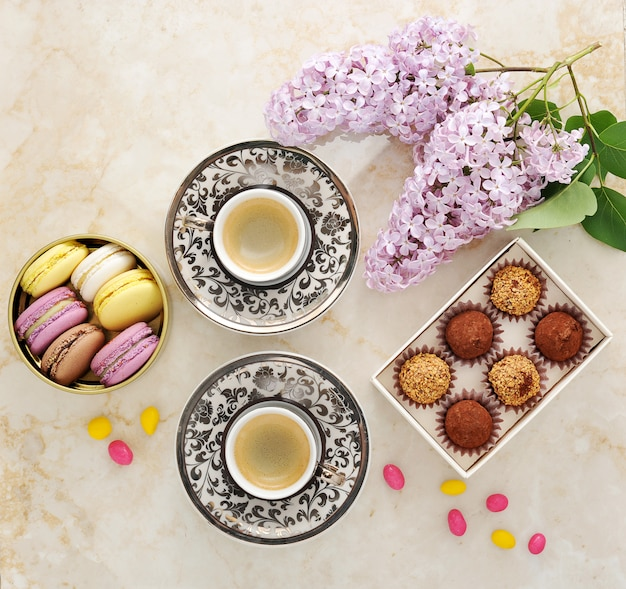 Morning coffee with cakes macarons and a branch of lilac