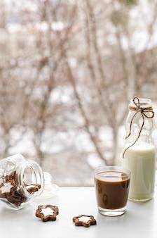 ウィンドウビューでミルクとチョコレートビスケットまたはクッキーとモーニングコーヒー