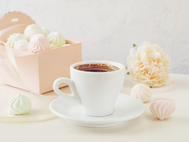 Morning coffee with a notebook and a box filled with small meringues on a wooden light background
