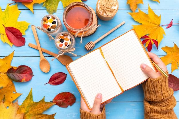 Morning coffee with yogurt and a notepad with autumn leaves.