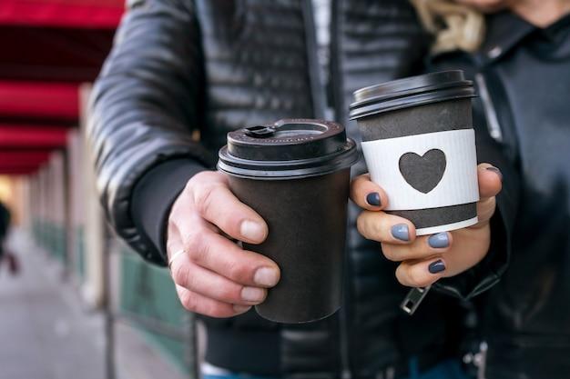모닝커피. 여자와 남자는 유리에 모양이 들리는 일회용 커피 컵을 들고 있습니다. 고품질 사진