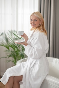 Morning coffee. woman in white robe having her morning coffee and looking pleased