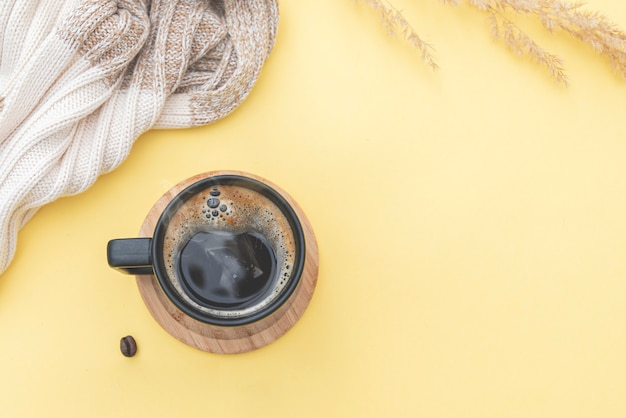 Morning composition scarf on table with coffee mug, coffee beans. autumn season