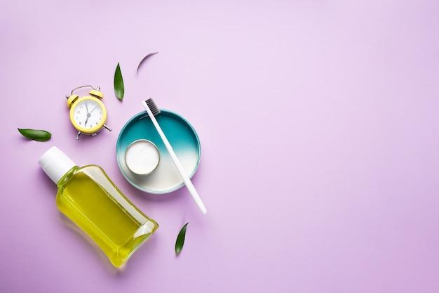 Утренняя концепция, будильник и зубные щетки крупным планом на фиолетовом