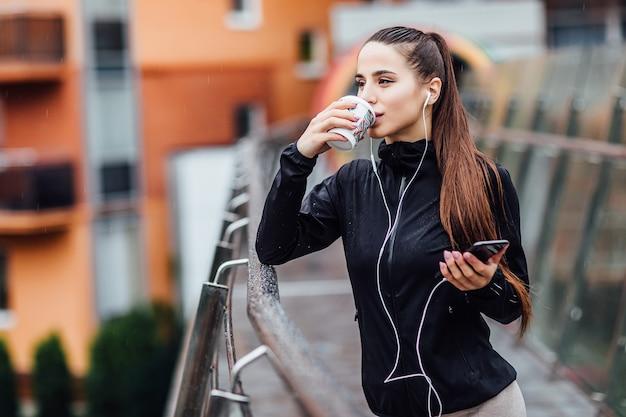 朝のコンセプト。コーヒーやお茶を持って走り、階段でリラックスした後の魅力的な女性。