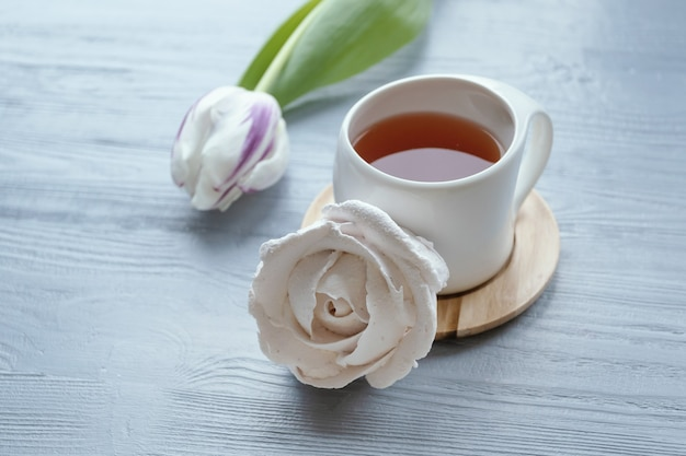 Утренняя концепция. чашка чая, зефир, тюльпан. белая чашка с чаем, розовыми тюльпанами и зефиром.