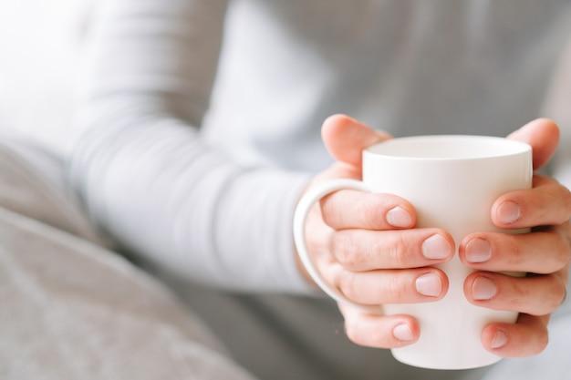 Утренний уют. мужчина в пижаме держит белую чашку любимого напитка.