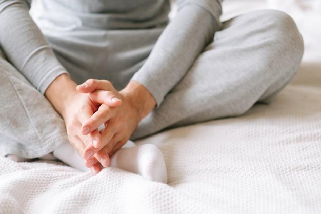 Утренний уют. впереди новый день. человек в серой пижаме сидит на кровати и думает.