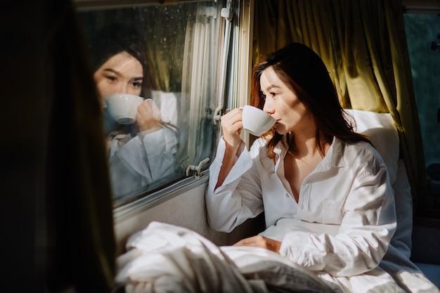 아침, 아늑함, 겨울, 그리고 사람들의 개념 - 침대에서 커피나 코코아 음료 한 잔과 함께 행복한 젊은 여성의 클로즈업