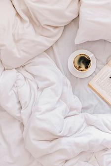 ベッドで朝の居心地の良いムードコーヒー白い毛布の上にベッドでブラックコーヒーのカップ