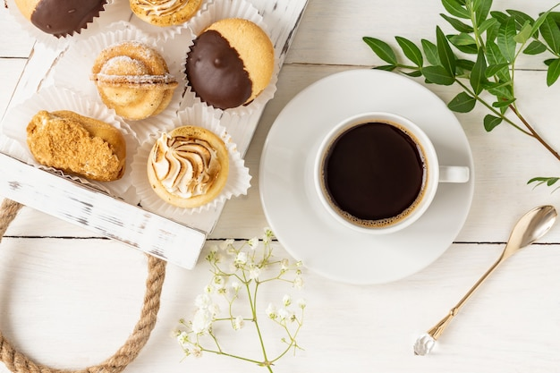Morning cup of coffe with tasty freshly baked desserts decorated with leaves and flowers.