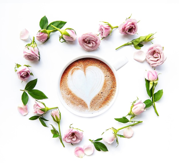 Morning cup of coffee and beautiful rose flowers on a white background