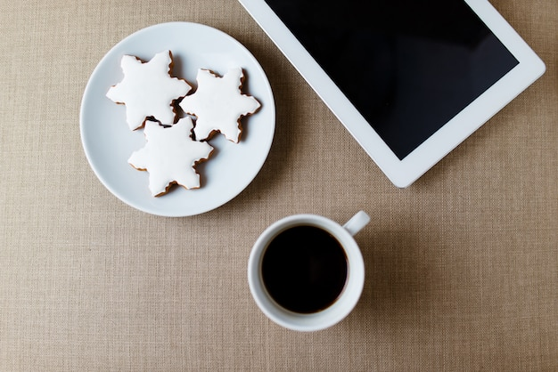 Morning cup of coffee on the shabby white desk with digital tablet with empty screen, candle, fresh cookie