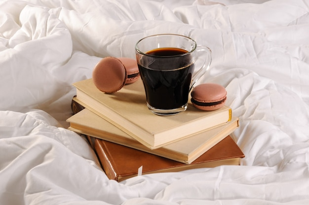 Morning cup of coffee with chocolate cakes macaroons, on a pile of books in bed.