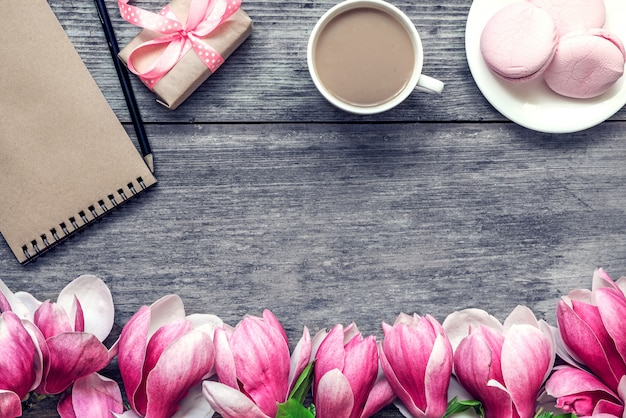 Morning cup of coffee with milk, cake macaron, gift or present box and magnolia flowers on rustic wooden table. flat lay