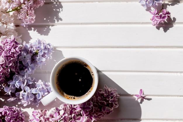아침에 블랙 커피 한 잔과 흰색 배경에 녹색 잎이 있는 보라색 라일락 꽃, 흰색 커피 한잔, 아름다운 라일락 꽃다발. 봄과 편안함의 개념입니다.