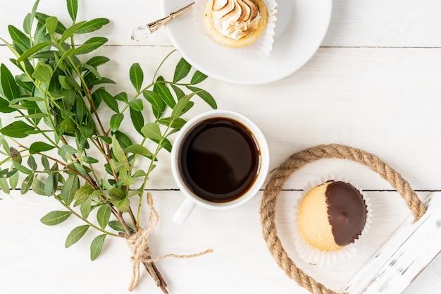 朝のコーヒーカップ、ミニデザート、緑の小枝の葉の束。上面図、軽くて風通しの良いフラットレイ。